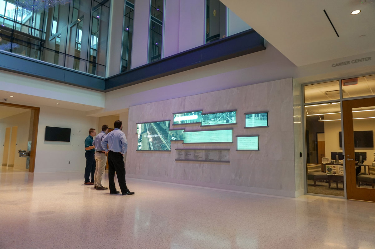 Spectators admiring the main digital donor recognition display inside Collat School of Business