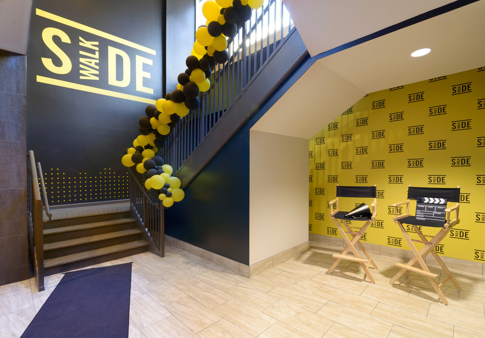 Entry area with step and repeat photo wall and branded wall graphics at Sidewalk Cinema